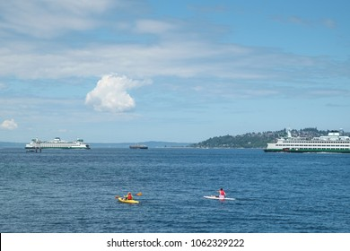 Seattle, WA, USA July 14, 2016: Two people on paddleboards share Puget Sound with two ferry boats and a cargo ship on a sunny day