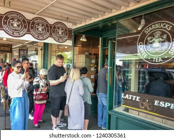 SEATTLE, WA, USA - JUNE 2018: People queuing outside the original Starbucks coffee shop in Pike Place in Seattle,