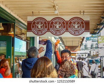 SEATTLE, WA, USA - JUNE 2018: People taking selfies while queuing outside the original branch of Starbucks in Pike Place, Seattle.