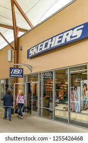 SEATTLE, WA, USA - JUNE 2018: Shoppers walking past the Skechers store at the Premium Outlets shopping mall near Seattle.