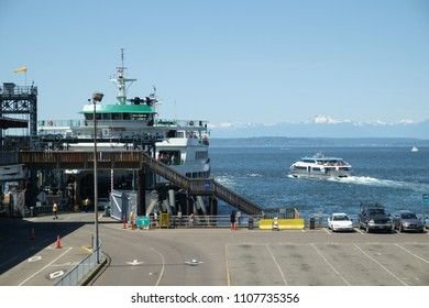 Seattle, WA, USA May 13, 2018: Pedestrian only fast ferry boat M/V Doc Maynard departs Pier 52 in Seattle while Jumbo class ferry M/V Tacoma finishes loading for a westbound crossing of Puget Sound