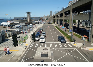 Seattle, WA, USA May 13, 2018: Seattle waterfront with homeless encampment beneath soon to be demolished Alaskan Way Viaduct on right and tourist on left