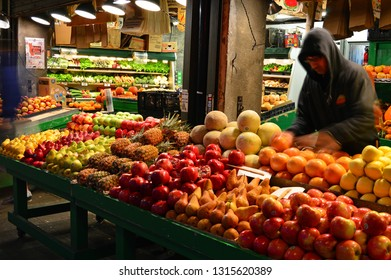 Seattle, WA, USA October 23, 2014 A adult male worker sets the fruit display at a public market in Seattle, Washington