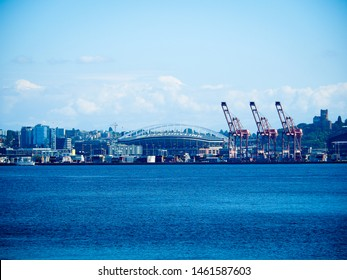 Seattle, WA USA - September 2017 : Port of Seattle and industrial district looking from Elliott Bay , with ferry terminal,cargo cranes,Century Link Field, Harbor Island background on bright blue sky