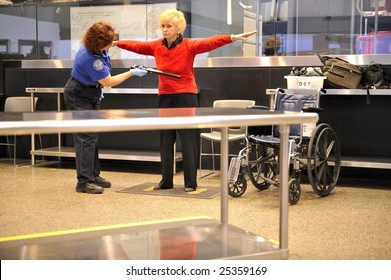 SEATTLE, WA-FEBRUARY 05:A TSA agent scans a passenger at Seattle-Tacoma International Airport (serving over 30 million people yearly) on February 05, 2009. The  poignant 9-11 message board is legible.