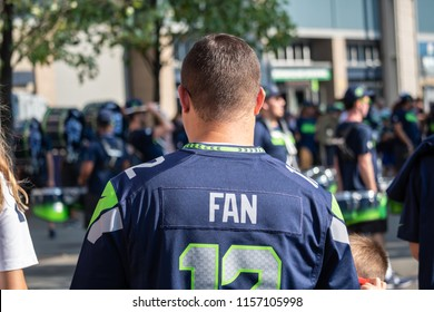 Seattle, Washington - 8/9/2018 : A fan in a 12th man fan watch the Blue Thunder drumline in front of CenturyLink Field before a Seattle Seahawks football game.