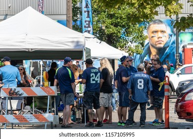 Seattle, Washington - 8/9/2018 : Seahawks fans tailgating in a parking lot before a game at Centurylink Field.