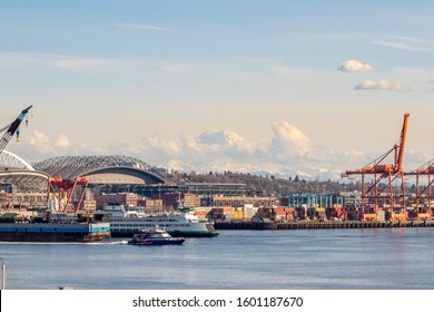 Seattle, Washington - Circa 2019: Clouds forming and moving in front of Mt. Rainier and part of the harbor island with containers in the Elliott Bay in Seattle, Washington on a beautiful day.