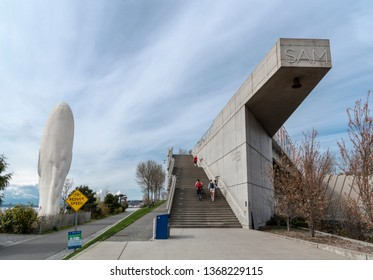 Seattle Washington circa April 2019 the waterfront sculpture park entrance with people walking up cement stairway under wispy blue sky.
