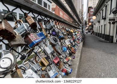 Seattle Washington circa April 2019, variety of different brand and style padlocks attached to a bridge path walkway.