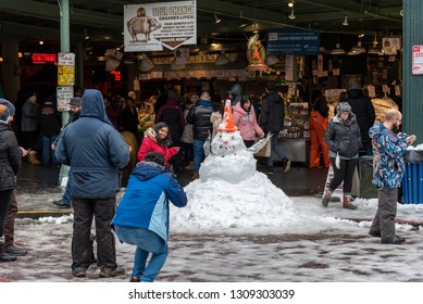 Seattle, Washington circa February 2019  Pike Place market covered in winter snow with tourists posing with fish monger constructed snowman.