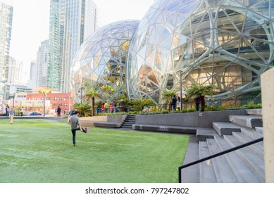 Seattle, Washington circa January 2018 the Amazon world headquarters campus with Spheres and employees playing frisbee on campus lawn.