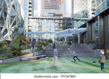 Seattle, Washington circa January 2018 the Amazon world headquarters campus showing outside lawn area showing employees on break enjoying a game of frisbee with Spheres terrariums.