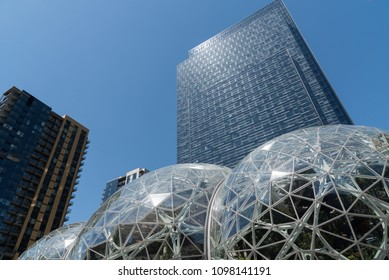 Seattle, Washington circa May 2018, Looking up at the Amazon company world headquarters office tower with green house Spheres at the base under clear blue mid day sunny sky with new construction.