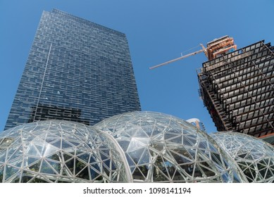 Seattle, Washington circa May 2018, Looking up at the Amazon company world headquarters office tower with green house Spheres at the base under clear blue mid day sunny sky.