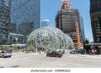 Seattle, Washington circa May 2018 Amazon company world headquarters campus on a sunny blue sky spring day, traffic and people at intersection next to Spheres terrariums.