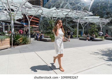 Seattle, Washington circa May 2018 Amazon company world headquarters campus on a sunny blue sky spring day, businesswoman talking on cell phone on outside sidewalk wearing white dress.
