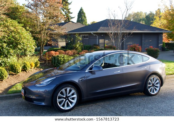 Seattle, Washington, circa November 2019.  A midnight sliver metallic Tesla Model 3 parked in front of an upscale home in the Windermere neighborhood.
