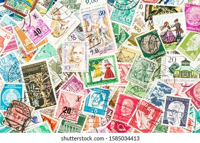 SEATTLE WASHINGTON - December 5, 2019:  Background of scattered used stamps of East and West Germany - Democratic and Federal Republics, Eastern and Western Bloc