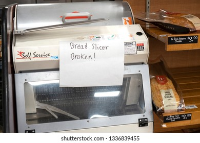 "Seattle Washington, March 10 2019. A hand written sign ""Bread slicer broken"" on a commercial bread slicer in Fred Meyer store."