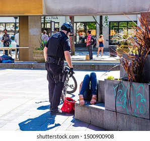 SEATTLE, WASHINGTON - May 20, 2017: A police officer on a bicycle talking to a drunk woman in Seattle's Westlake Park