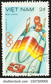 SEATTLE, WASHINGTON - September 16, 2019: Close up of used postage stamp from Vietnam celebrating events at the XIV Winter Olympics of Sarajevo: Men's bobsled team.