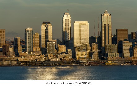 Seattle, Washington Skyline. Shot from West Seattle over Elliott Bay during a dramatic and lovely sunset. Ferryboats cross Elliott Bay heading to Bainbridge Island filled with commuters.