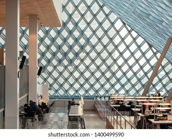 Seattle, Washington, United States of America - December 26 2017: Seattle Public Library designed by famous architect Rem Koolhaas. People reading books or studying. Notable work of architecture.