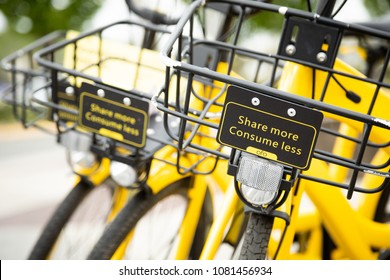 Seattle, Washington/ USA - April 30, 2018: Close up on the handle bar basket with Share More Consume Less sign, on a yellow Ofo bike, part of an app based bicycle sharing network