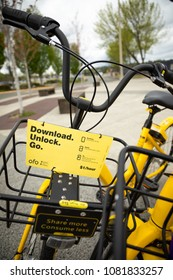 Seattle, Washington/ USA - April 30, 2018: Close up on the handle bars and Download Unlock Go instruction sign, for a yellow Ofo bike, part of an app based bicycle sharing network