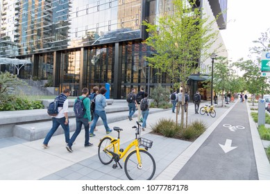 Seattle, Washington USA circa April 2018 The Amazon World Headquarters Campus Spheres terrariums afternoon light in spring season showing group of employees walking on grounds with commuter bike.
