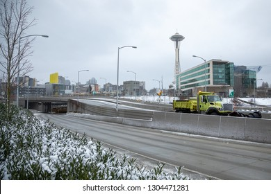 Seattle, Washington / USA - February 4 2019: Snow plow exiting the new State Route 99 Tunnel under downtown Seattle, with Space Needle in the background, during a snowstorm on opening day