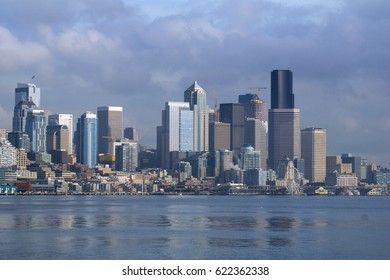 SEATTLE, WASHINGTON, USA - JAN 25th, 2017: A view on Seattle downtown from the waters of Puget Sound. Piers, skyscrapers and Ferris wheel in Seattle city before sunset