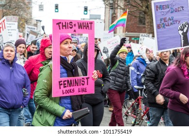 Seattle, Washington / USA - January 20, 2018: Womxn March. Marchers hold up hand written protest signs.