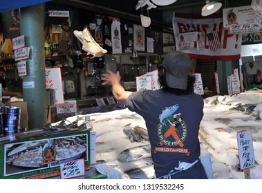 Seattle, Washington / USA - July 1, 2015: A fishmonger entertaining tourists by tossing a fish at the famous Pike Place Fish Market.