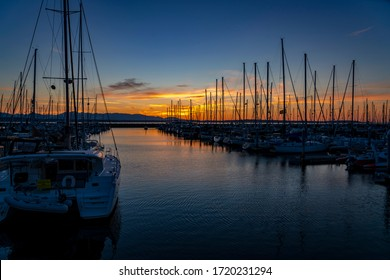 Seattle, Washington / USA - July 22, 2018: Small boats, safely tied up in slips rest for the night as the sun sets over Puget Sound and Shilshole Bay Marina near Seattle, Washington.