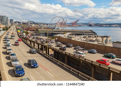 Seattle, Washington, USA - July 6, 2018: Traffic on Alaskan Way with The Seattle Great Wheel Ferris and Pier 57 visible in background, Seattle, Washington, USA