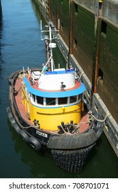 SEATTLE, WASHINGTON, USA JULY 7, 2017: Small red, yellow, and blue tug boat enters the small lock at Hiram Chittenden Locks (Ballard Locks) in Seattle to transit from Puget Sound to Salmon Bay