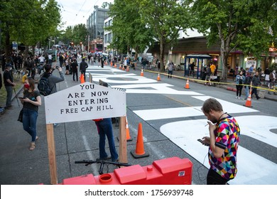 """Seattle, Washington / USA - June 10 2020: """"You Are Now Entering Free Cap Hill"""" beside a """"Blacks Lives Matter"""" mural  at the Capitol Hill Occupied Protest (CHOP)"""
