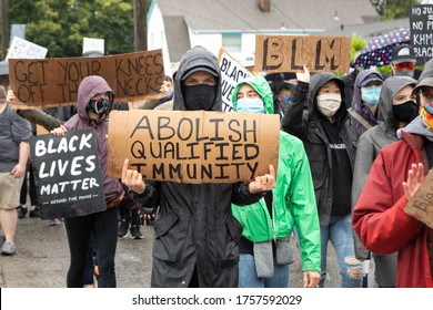 """Seattle, Washington / USA - June 12 2020: Protester with """"Abolish Qualified Immunity"""" sign at the March of Silence in support of Black Lives Matter"""