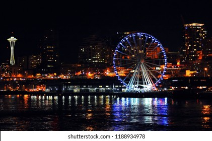 """Seattle, Washington / USA - March 8, 2015: Seattle's """"Great Wheel"""" at night, with the city's skyline and Space Needle in the background, March 8, 2015."""