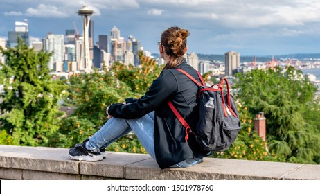 SEATTLE, WASHINGTON, USA. Young lady backpacker tourist alike visiting Queen Anne Hill's Kerry Park to catch a spring sunset over downtown Seattle and Mt. Rainier in the background.
