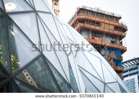 SEATTLE, WASHINGTON/USA - April 14, 2018: Close up on the geometric windows on the glass Spheres at the Seattle Amazon headquarters, with a new Amazon office tower under construction in the background