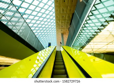 Seattle, Washington/USA - November 23, 2019: Ascending a brightly colored escalator into a cavernous canopy of geometric glass and steel at the Seattle Central Public Library.