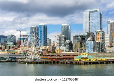 Seattle waterfront, piers 56 and 57, and skyline on a bright and cloudy day, view from the Puget Sound, Washington State, USA.