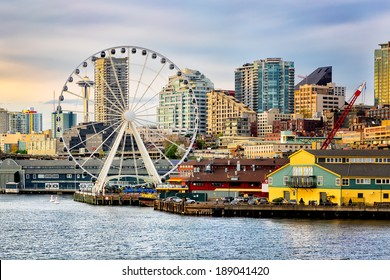 Seattle waterfront and skyline, with the Space Needle showing through the spokes of the Great Wheel ferris wheel in the foreground. Colorful image with late afternoon gold light.