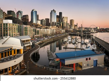 Seattle Waterfront at Sunset. The Seattle, Washington waterfront and skyline at sunset with a marina and ferris wheel. The Port of Seattle can be seen in the background.