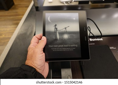 Seattle, WA/USA-6/15/19: A person holding an  Amazon Kindle Oasis device that is on sale at an Amazon Book Store.