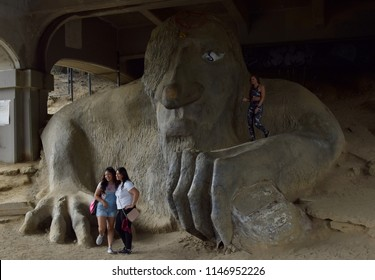 Seattle, WA/USA-7/1/18 - Tourists pose for photos around the Fremont Troll. Public art sculpture features concrete monster holding a real Volkswagen Beetle.