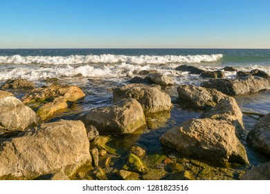 Seaview with rocks, waves and clear blue sky, Alassio, Liguria, Italy